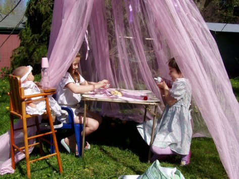 Two girls and a doll having a tea party under a pink tent hanging from a tree.