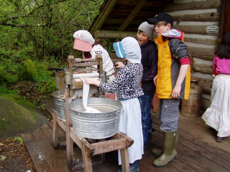 two students in sun bonnets using washtubs outside a cabin, while two others watch