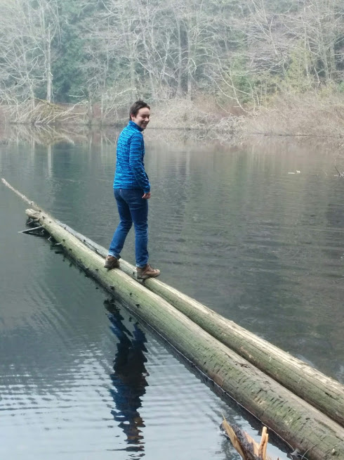 Out on two limbs. Logs. Woman balanced on two logs sticking out into a lake.