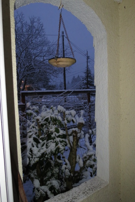 archway in the evening, with a hanging birdbath and snow on a yard, all blue light